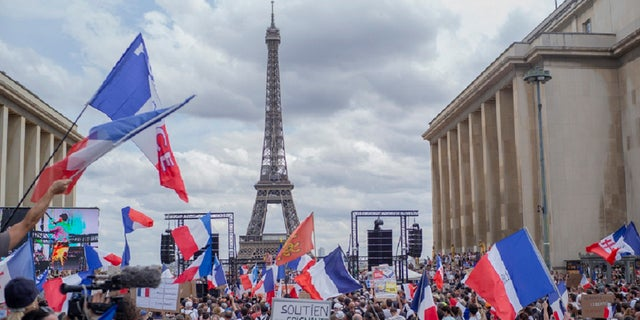 Thousands of protesters gather at Place Trocadero near the Eiffel Tower attend a demonstration in Paris, France, Saturday July 24, 2021, against the COVID-19 pass which grants vaccinated individuals greater ease of access to venues.