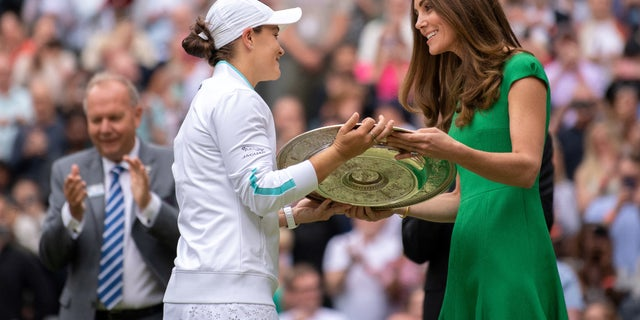 Australia's Ashleigh Barty receives the trophy from Britain's Catherine, Duchess of Cambridge, after defeating Karolina Pliskova of the Czech Republic in their female final match on the twelfth day of the 2021 Wimbledon Championship at The All England Tennis Club in Wimbledon, southwest London, on 10 July , 2021. (Photo by AELTC / BEN SOLOMON / POOL / AFP via Getty Images)