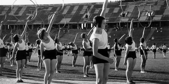 Women entered the Olympic gymnastics space during the Berlin 1936 Summer Olympics. This file photo shows gymnasts performing at the Olympic Stadium with rings.