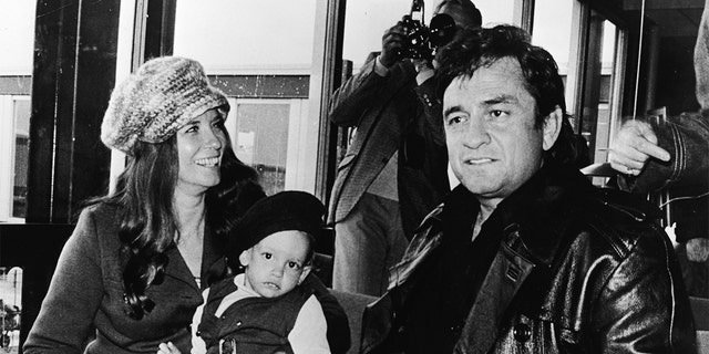 American country singer Johnny Cash (1932 - 2003) sits inside an airport with his wife June Carter Cash (1929 - 2003) and their infant son John Carter Cash, as the singer arrived in Copenhagen, Denmark to begin his Scandinavian tour, circa 1971.