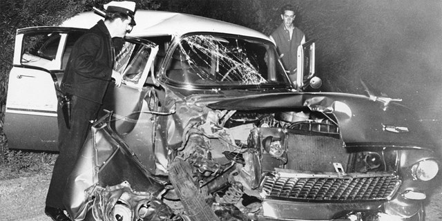 A policeman investigates the wreckage of actor Montgomery Clift's car after it collides with an electric pole after a dinner party at the home of Michael Wilding and Elizabeth Taylor.  Clift suffered serious head injuries.