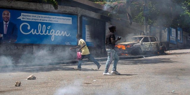 People move past a burning truck outside the police station of Petion Ville during a protest against the assassination of Haitian President Jovenel Moïse in Port-au-Prince, Haiti, Thursday, July 8, 2021. Officials pledged to find all those responsible for the pre-dawn raid on Moïse's home early Wednesday in which the president was shot to death and his wife, Martine, critically wounded. (AP Photo)