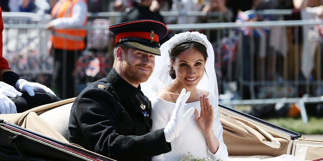 Prince Harry, Duke of Sussex and Meghan, Duchess of Sussex wave from the Ascot Landau Carriage during their carriage procession on Castle Hill outside Windsor Castle on May 19, 2018 in Windsor, England.