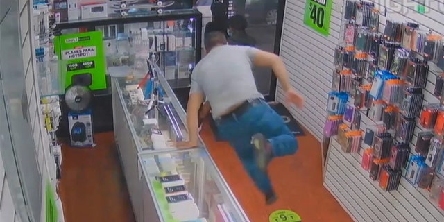 A Queens cellphone store employee jumped over the counter to stop a trio of crooks — and ended up getting robbed himself, according to cops and surveillance video.