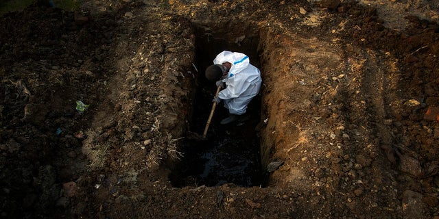 A man in protective suit digs earth to bury the body of a person who died of COVID-19 in Gauhati, India, on April 25. (AP)