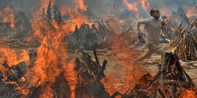 A man runs to escape heat emitting from the multiple funeral pyres of COVID-19 victims at a crematorium in the outskirts of New Delhi, India, on April 29.