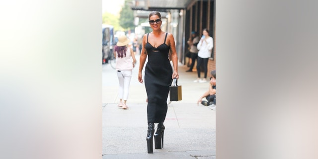 Lady Gaga stuns in a black dress and high platform heels as she comes out from the studio in New York.