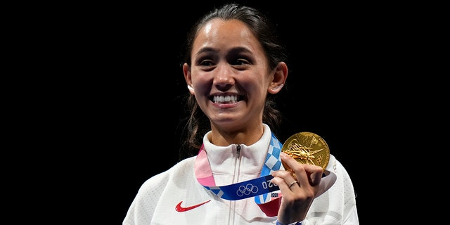 Gold medalist Lee Kiefer of the United States, holds her gold medal during the medal ceremony for the women's individual Foil final competition at the 2020 Summer Olympics, Sunday, July 25, 2021, in Chiba, Japan. (Associated Press)