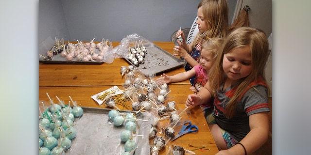Madsen's daughters' preparing cake pops for the lemonade stand.