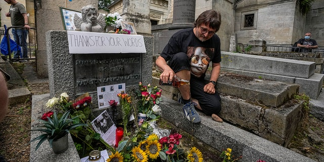 German Torsten Marquardt pours whiskey at the grave of rock singer Jim Morrison at Père-Lachaise cemetery in Paris, on Saturday July 3, 2021. (Associated press)