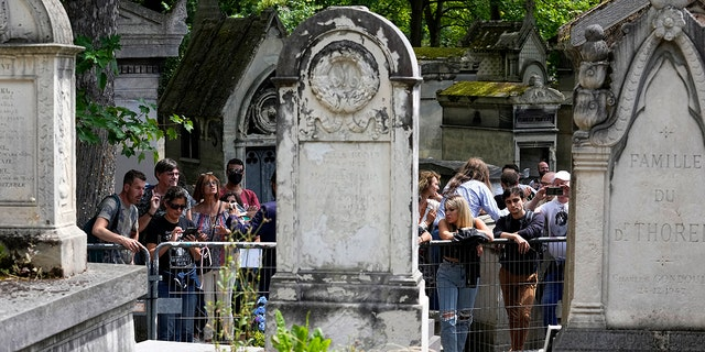 Fans gather at the grave of rock singer Jim Morrison at Père-Lachaise cemetery in Paris on Saturday, July 3, 2021. (Associated press)