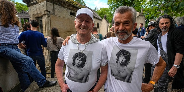 Fred Verheijden, left, and Hans van Schie from the Netherlands wear shirts with a photo of the late rock singer Jim Morrison at Père-Lachaise cemetery in Paris on Saturday July 3, 2021. (Associated press)