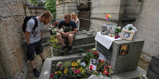 Joachim Tittmar from Germany, left, Walter Homburg from the Netherlands, center, and his girlfriend Kate Schirm meet at the grave of rock singer Jim Morrison at Père-Lachaise cemetery in Paris on Saturday July 3, 2021 (Associated press)