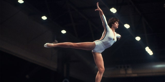 Nadia Comaneci from Romania competed in the balance beam event at the Moscow 1980 Summer Olympics with a white leotard that had colorful stripes that represented her home country.