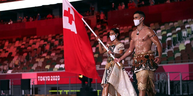 Malia Paseka and Pita Taufatofua from Tonga carry the flag of their country during the opening ceremony at the Olympic Stadium of the 2020 Summer Olympics on Friday, July 23, 2021, in Tokyo, Japan. (Hannah McKay / Pool Photo via AP)