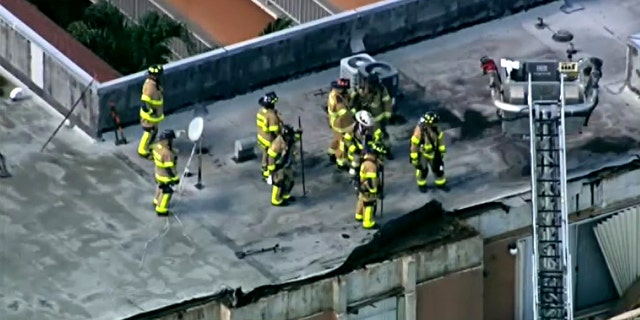 Firefighters on the roof of a Northwest Miami-Dade apartment building roof collapse Thursday.