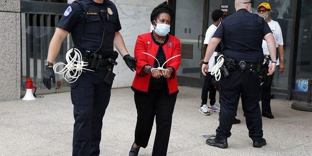 La representante estadounidense Sheila Jackson Lee, demócrata de Texas, es arrestada por un miembro de la policía del Capitolio de los Estados Unidos por participar en desobediencia civil durante una protesta frente al edificio de oficinas del Senado Hart en el Capitolio, 29 de julio de 2021 (Getty Images)