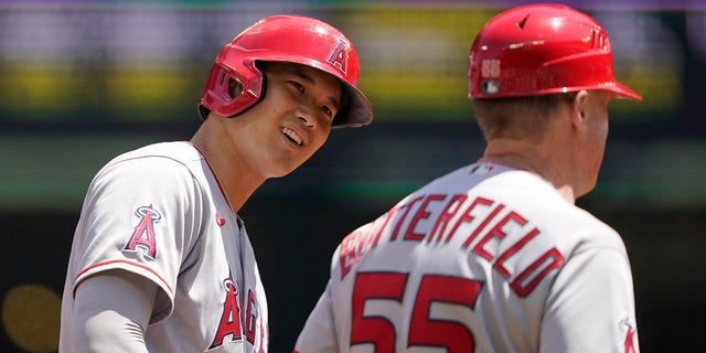 Los Angeles Angels' Shohei Ohtani, left, talks with third base coach Brian Butterfield while on base during the first inning of a baseball game against the Seattle Mariners, Sunday, July 11, 2021, in Seattle. (AP Photo/Ted S. Warren)
