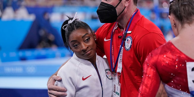 Coach Laurent Landi embraces Simone Biles after she exited the team final with apparent injury at the 2020 Summer Olympics, Tuesday, July 27, 2021, in Tokyo. The 24-year-old reigning Olympic gymnastics champion Biles huddled with a trainer after landing her vault. She then exited the competition floor with the team doctor. (AP Photo/Gregory Bull)