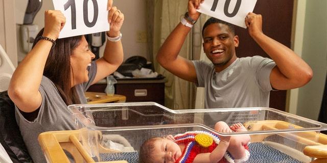 Parents celebrating their newborn's birth amid the Tokyo Olympics.