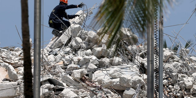 SURFSIDE, FLORIDA - JULY 09: A rescue worker guides an excavator to dig through the remains from the collapsed 12-story Champlain Towers South condo building on July 09, 2021 in Surfside, Florida. (Photo by Anna Moneymaker/Getty Images)