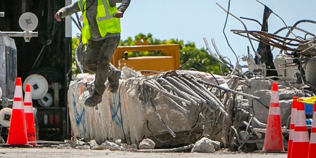 A worker jumps off a large piece of rubble on the site of the Champlain Towers South collapse, in Surfside, Fla., on Monday.
