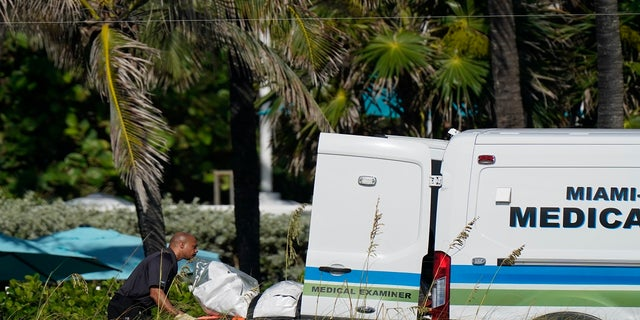 Workers load a stretcher with remains extricated from the rubble into a Miami-Dade County Medical Examiner van, near the Champlain Towers South condo building on Friday. (AP)