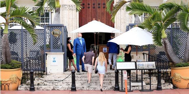 Una pareja ingresa a The Villa Casa Casuarina en The Former Versace Mansion en Ocean Drive el 3 de julio de 2020 en el vecindario de South Beach en Miami Beach, Florida.  (Foto de Cliff Hawkins / Getty Images)