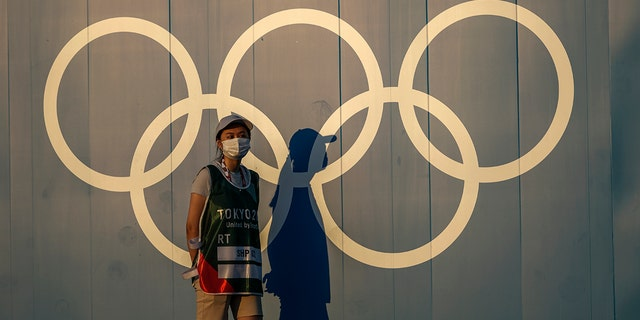 A volunteer walks past the Olympic rings ahead of the 2020 Summer Olympics, on Thursday, July 22, 2021, in Tokyo Japan.(AP Photo/Petros Giannakouris)