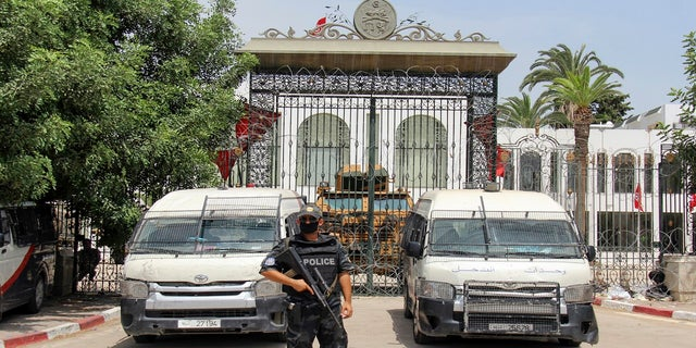 Police cars and a military armored personnel carrier block the entrance of the Tunisian parliament in Tunis on Tuesday.