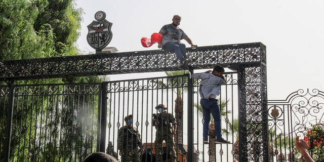 Tunisian soldiers guard the main entrance of the parliament as demonstrators gather outside the the gate in Tunis, Tunisia, on Monday.