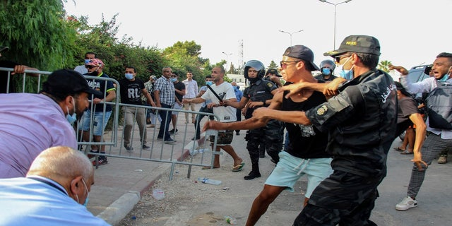 Tunisian police officers scuffle with demonstrators as they gather outside the parliament in Tunis, Tunisia, on Monday.