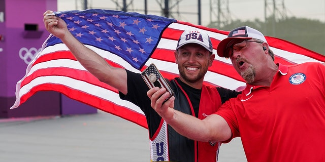 Gold medalist Vincent Hancock, of the United States, takes a selfie with his coach after the men's skeet at the Asaka Shooting Range in the 2020 Summer Olympics, Monday, July 26, 2021, in Tokyo. (Associated Press)