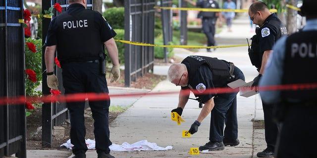 La police enquête sur une scène de crime où trois personnes ont été abattues dans le complexe de logements Wentworth Gardens dans le quartier de Bridgeport le 23 juin 2021 à Chicago, Illinois.  Un homme de 24 ans est décédé des suites des blessures qu'il a subies lors de la fusillade et deux autres, un homme de 22 ans et un homme de 25 ans, ont été grièvement blessés.