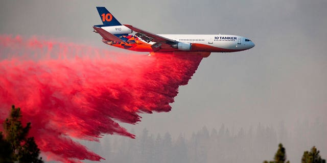 In this photo provided by the Bootleg Fire Incident Command, a DC-10 tanker drops retardant over the Bootleg Fire in southern Oregon, Thursday, July 15, 2021. (Bootleg Fire Incident Command via AP)