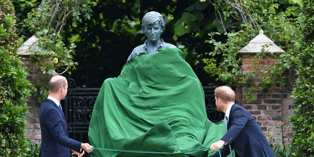 Britain's Prince William, left and Prince Harry unveil a statue they commissioned of their mother Princess Diana, on what woud have been her 60th birthday, in the Sunken Garden at Kensington Palace, Londen, Thursday July 1, 2021.