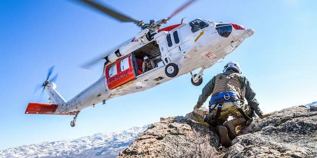 """FILE PHOTO - FALLON, Nev. (April 8, 2021) An MH-60S Knighthawk helicopter assigned to the """"Longhorns"""" of Helicopter Search and Rescue (SAR) Squadron, practices pinnacle landings and extractions during a mountain flying SAR training event. (U.S. Navy photo by Chief Mass Communication Specialist Shannon Renfroe)"""