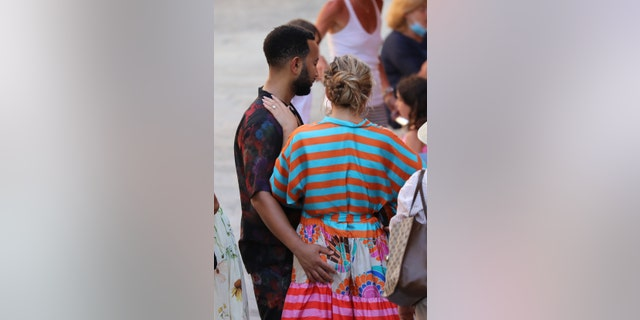 John Legend gives sweet wife Chrissy Teigen an ass hug as the couple steps out during their Italian escape on July 6th.