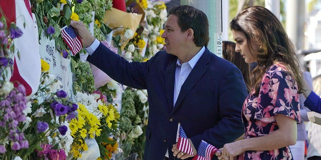 Florida Gov. Ron DeSantis and his wife Casey leave flags at a makeshift memorial near the Champlain Towers South condo building, where scores of victims remain missing more than a week after it partially collapsed, Saturday, July 3, 2021, in Surfside, Florida.