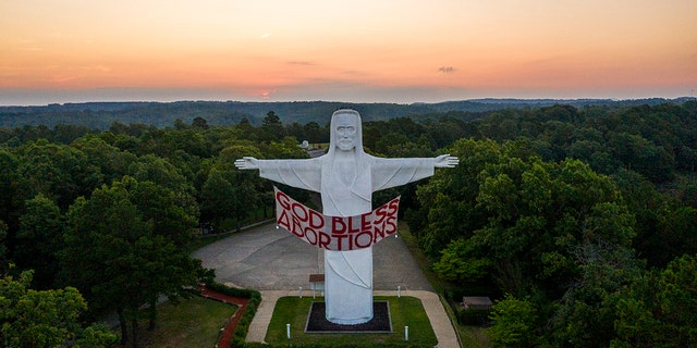 An activist art group called Indecline hung this banner at the Christ of the Ozarks statue in Eureka Springs, Arkansas on Thursday night.