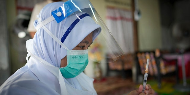 July 13, 2021: A nurse prepares to administer a Pfizer COVID-19 vaccine to an elderly woman in her house in rural Sabab Bernam, central Selangor state, Malaysia.