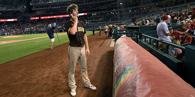 San Diego Padres player Will Myers talks on a cell phone during the pause of play due to a shootout near the ballpark during the sixth inning of a baseball game between the Washington Nationals and Padres on Saturday, July 17, 2021 in Washington.  (The Associated Press)