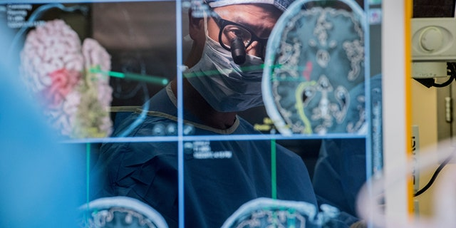 In this 2017 photo provided by the University of California, San Francisco, neurosurgeon Dr. Edward Chang is reflected in a computer monitor displaying brain scans as he performs surgery at UCSF.