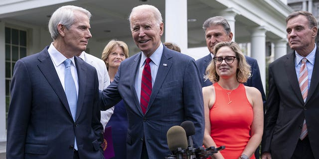 File - President Joe Biden, Republican Senator Rob Portman from Center, Ohio, on the left, Democrat Senator Mark Warner from Virginia, speaking to members of the media, from the right, Democrat Senator Kirsten Cinema from Arizona, Senator Westminch from West Virginia Republican Senator Lisa Murkowski from Alaska, outside the West Wing of the White House after a meeting on Thursday, June 24, 2021, in Washington, DC, USA.