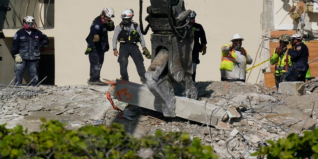 Heavy machinery is used to remove a support column as search and rescue personnel work atop the rubble at the Champlain Towers South condo building on Friday. (AP)