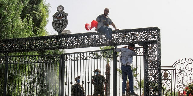 Tunisian soldiers guard the main entrance of the parliament as demonstrators gather outside the the gate in Tunis, Tunisia, Monday, July 26, 2021. (AP Photo/Hedi Azouz)