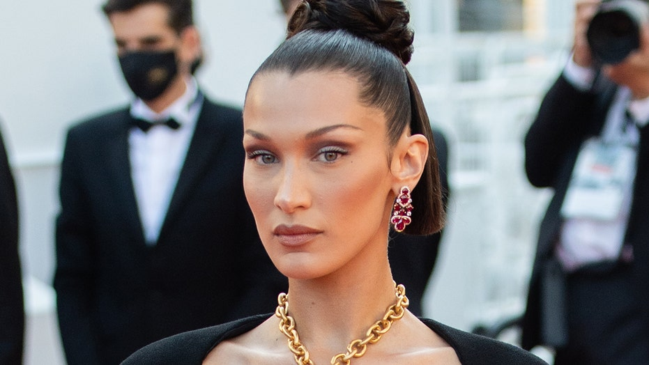 Bella Hadid covers breasts with golden lungs necklace at Cannes