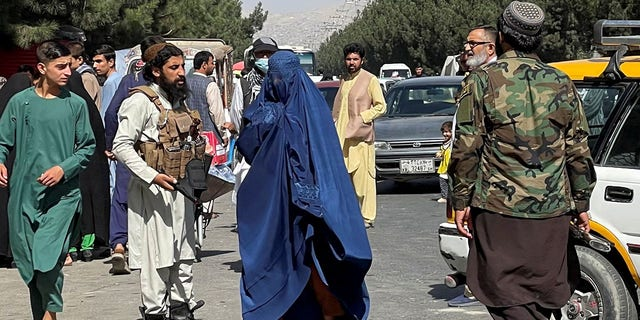 Taliban forces block the roads around the airport, while a woman with Burqa walks passes by, in Kabul, Afghanistan. August 27, 2021. REUTER/Stringer