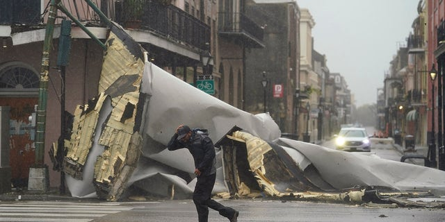 A man passes by a section of roof that was blown off of a building in the French Quarter by Hurricane Ida winds, 日曜日, 8月. 29, 2021, in New Orleans. (AP Photo/Eric Gay)