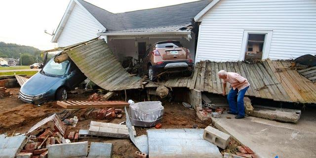 Ernest Hollis busca artículos en la casa de su nieta que fue devastada por las inundaciones el lunes 23 de agosto de 2021 en Waverly, Tennessee.